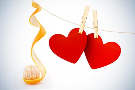 orange peel skin: Hearts hanging on line against orange peeled on a orange peel