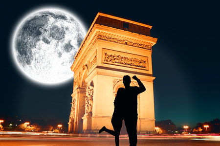 Attractive couple smiling and cheering against large moon over arc de triomph photo