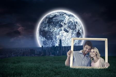 Attractive young couple holding picture frame against bright moon over city photo