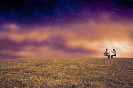 Sitting couple having an argument against aurora night sky in purple photo