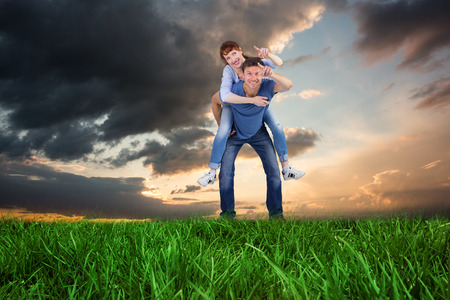 Man giving girl a piggy back against blue and orange sky with clouds photo
