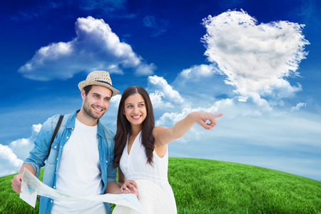 Happy hipster couple looking at map against cloud heart photo