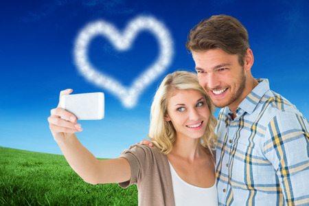 Attractive couple taking a selfie together against green field under blue sky photo