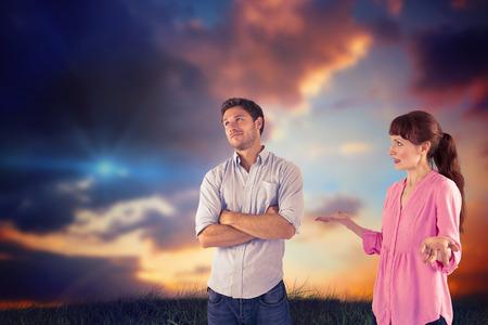 pareja discutiendo: Mujer que discute con el hombre insensible contra el cielo azul y naranja con las nubes Foto de archivo