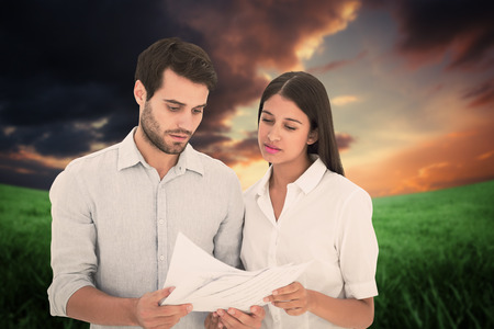 figuring: Attractive young couple reading their bills against green field under orange sky Stock Photo