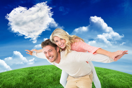 Handsome man giving piggy back to his girlfriend against cloud heart photo