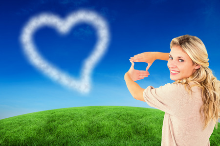 framing: Attractive young blonde framing with her hands against green hill under blue sky