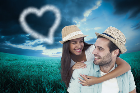 Happy casual man giving pretty girlfriend piggy back against blue sky over green field photo