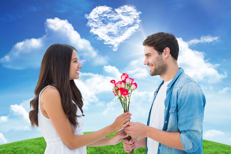 Happy hipster giving his girlfriend roses against cloud heart photo