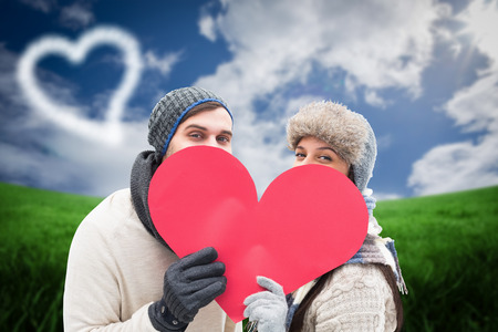 Attractive young couple in warm clothes holding red heart against green field under blue sky photo
