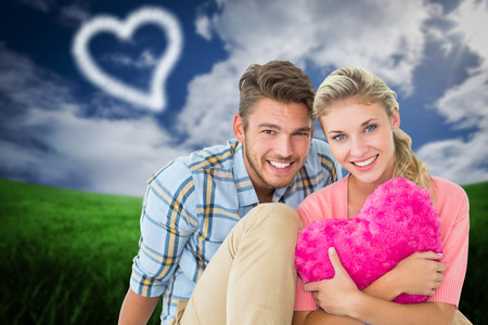 Attractive young couple sitting holding heart cushion against green field under blue sky photo