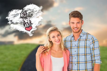 Attractive young couple smiling at camera against cloud heart photo