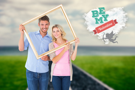 Attractive young couple holding picture frame against cloud heart photo