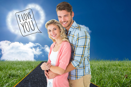 Attractive couple embracing and smiling at camera against road on grass photo