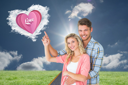 Attractive young couple embracing and pointing  against cloud heart photo