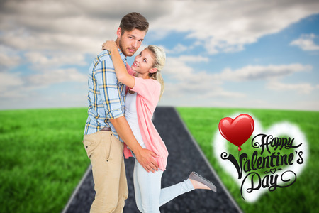Handsome man hugging his girlfriend against road on grass photo