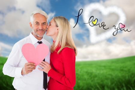 recibo: Hombre guapo celebración de corazón de papel consigue un beso de la mujer contra el campo verde bajo el cielo azul