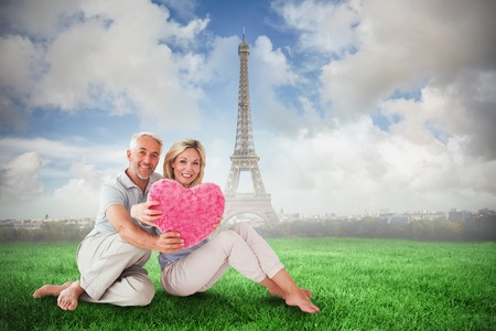 Happy couple sitting and holding heart pillow against eiffel tower photo