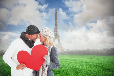 Smiling couple in winter fashion posing with heart shape against eiffel tower photo