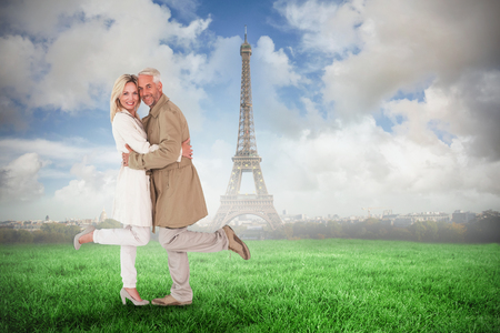trench: Happy couple posing in trench coats against eiffel tower