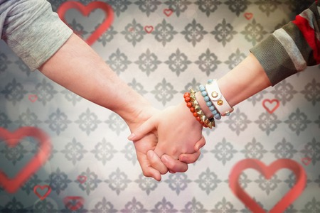 loving hands: Students holding hands against love heart pattern
