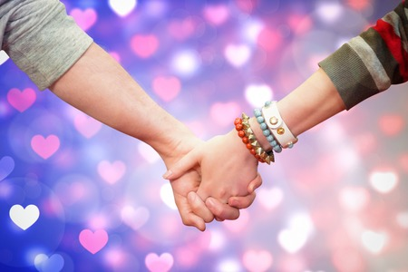 clasping: Students holding hands against valentines heart pattern Stock Photo