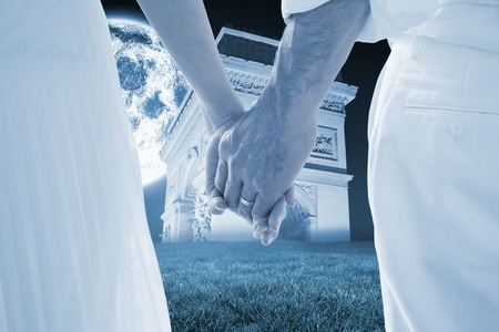 Bride and groom holding hands close up against bright moon over arc de triomph photo