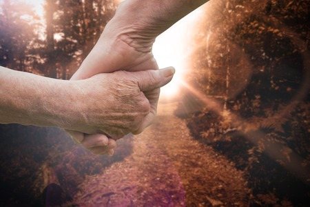 Elderly couple holding hands against forest trail Stock Photo