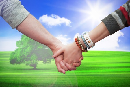 clasping: Students holding hands against sunny green landscape Stock Photo