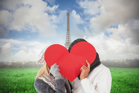 Couple in winter fashion posing with heart shape against eiffel tower photo