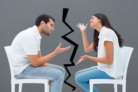 exasperated: Couple sitting on chairs arguing against grey Stock Photo