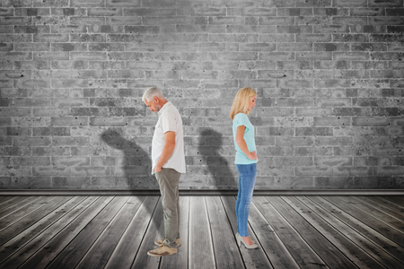 not lined: Unhappy couple not speaking to each other  against grey room Stock Photo