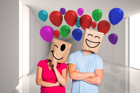 Young couple with bags over heads against digitally generated room with bright light 版權商用圖片 - 35902485