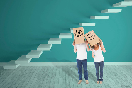 wonky: Mature couple wearing boxes over their heads against steps in a blue room Stock Photo