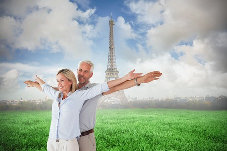 Happy couple standing with arms outstretched against eiffel tower photo