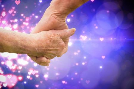 Elderly couple holding hands against valentines heart design Stock Photo