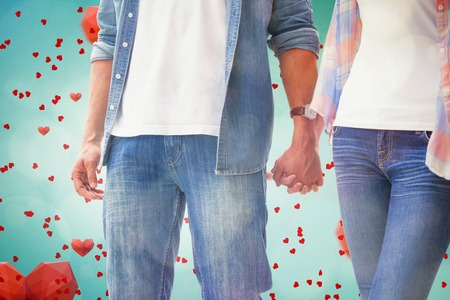 Hip young couple holding hands against love heart pattern photo