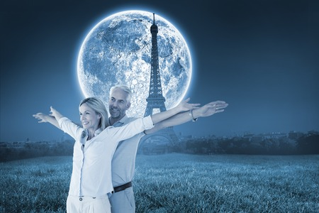Happy couple standing with arms outstretched against large moon over paris photo