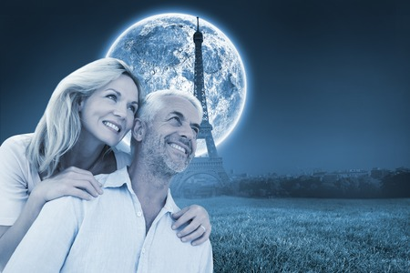 Smiling couple embracing and looking  against large moon over paris photo