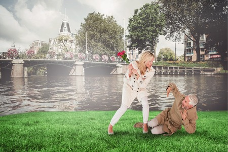 outraged: Angry woman attacking partner with rose bouquet against sunny day by the river Stock Photo