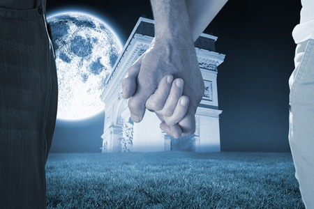 Happy senior couple holding hands against bright moon over arc de triomph photo