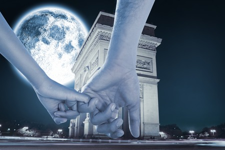 Loving young couple holding hands against large moon over arc de triomph photo