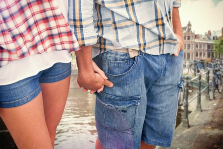hot pants: Couple in check shirts and denim holding hands against canal in amsterdam