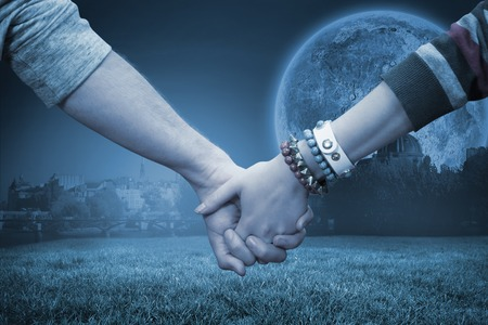clasping: Students holding hands against bright moon over paris