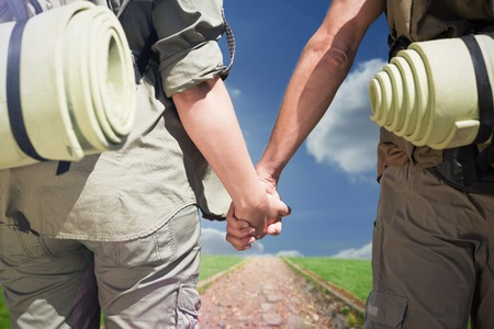 hitch: Hitch hiking couple standing holding hands on the road against path on grass Stock Photo