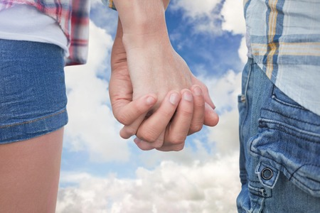 hot pants: Couple in check shirts and denim holding hands against blue sky with white clouds Stock Photo