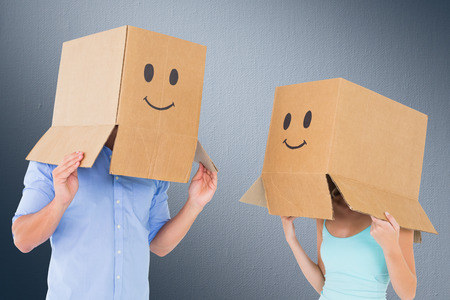 covering face: Couple wearing emoticon face boxes on their heads against digitally generated grey vignette background
