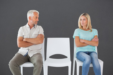 exasperated: Unhappy couple not speaking to each other  against grey