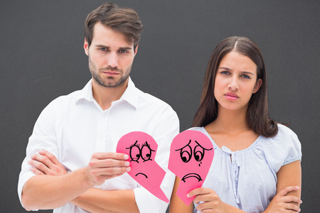 heart problems: Upset couple holding two halves of broken heart against grey Stock Photo