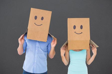 cabeza de mujer: La pareja llevaba cajas cara emoticon sobre sus cabezas contra gris